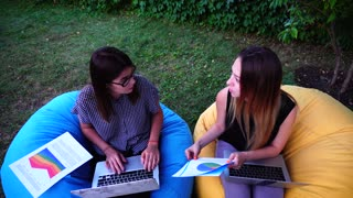 Portrait of Two Female Web Designers Who Design Web Interfaces For Sites Sitting in Outdoor Park in Park During Day.