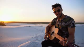 Portrait of young Muslim man who plays music on guitar among sandy desert at sunset in open air on summer evening