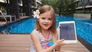 Pretty female child showing selfie on tablet near swimming pool. Concept of using front facing camera on modern gadget and enjoying summertime weather. Little girl has flower in hair.