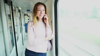 Pretty girl chatting on cell phone with girlfriend and laughs, smiles and shows thumbs-up gesture, looks at large window of fast modern train and stands in corridor with backpack on shoulder, begins