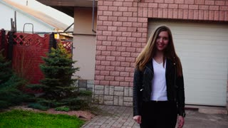 Pretty girl walking near garage in slow motion and smiling. Concept of fashion look and good mood. Young female person dressed in black leather jacket has long brown hair.