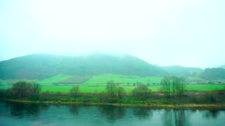 Pretty green landscape opens from train window at speedy cloudy autumn day.  Rushing transport rides past long river and on other side of river on opposite shore are green fields and meadows with tal