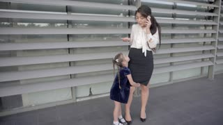 Pretty Modern Mother Talking on Phone, Little Girl Hugging Mother and They Stand Against Window of Business Center Outdoors in Neutral Colors.
