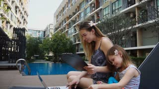 Pretty mother working with documents and laptop in slow motion near swimming pool and little daughter. Concept of businesswoman on exotic resort and modern gadgets. Young female person and child has