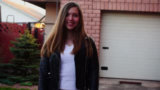 Pretty smiling girl passing with close up face near house in slow motion. Concept of spring weather and happy female person. Young woman wears black leather jacket and white shirt.