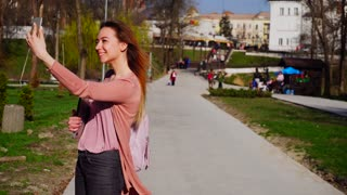 Pretty student making selfie by smartphone in slow motion and keeping laptop. Concept of modern gadgets, front facing camera and youth. Young female person walking after classes.