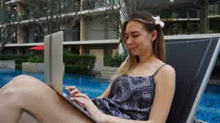 Pretty woman lying in beach chair and chatting by laptop with swimming pool background. Concept of communicating with friends abroad and cheap resort in Indonesia. Young female person has flower in