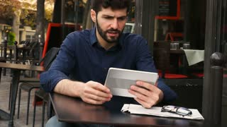 Prosperous man winning in online game with tablet at cafe table