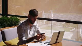 Prosperous sales manager reading documents, using laptop at table and calling with smartphone