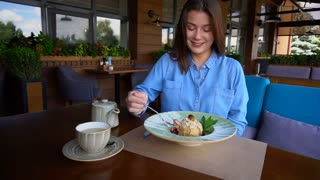 Satisfied girl eating dessert at restaurant in slow motion