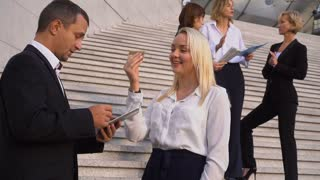 Secretary talking with boss keeping tablet on stairs with employees in background