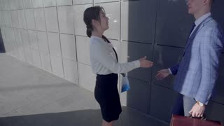 Self-Confident Girls and Guy Walk and Talk,bring in Hands Documentation on Background of Wall of Business Center Outside in Neutral Colors.