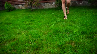 Shooting Closeups of Feet of Young Girl Who Leads One Foot on Grass Outdoors in Daytime.