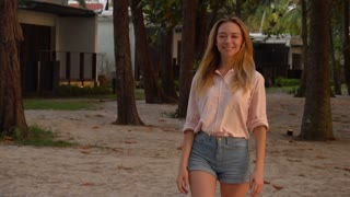 Slow motion actress walking near houses nearby sea, attractive girl smiling posing for advertisement of summer clothes. Concept of vacation at seaside, travelling and beachwear. Pretty slim lady