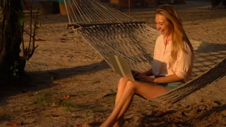 Slow motion architect lady with laptop sitting on hammock, smiling girl on vacation texting with sister rejoicing at good news. Concept of innovative technologies, communication and travelling. Fair