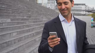 Slow motion business man walking using smartphone to watch photos