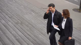 Slow motion CEO of big company man talking on smartphone and secretary woman climbing stairs