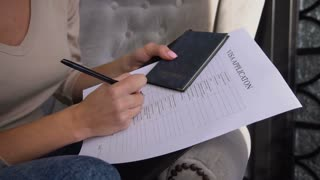 Slow motion female with visa application and passport filling form, bride preparing for honeymoon. Attractive smiling lady with ponytail sitting on grey chair writing dreaming about trip. Concept of