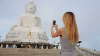 Slow motion journalist female making photos on smartphone, fair-haired lady taking pictures of Buddha s statue in Thailand. Concept of gadgets, international cooperation and travelling. Young woman
