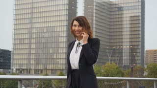 Slow motion journalist woman in business clothes talking on smartphone go to work