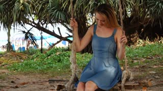 Slow motion law student girl relaxing, pretty young woman in blue sundress swinging in garden. Concept of travelling, vacation and tourism. Fair-haired girl enjoying good sunny weather dreaming about