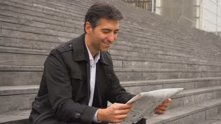 Slow motion male business tutor sitting on stairs and reading newspapers