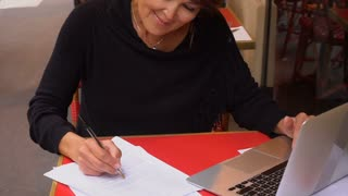 Slow motion middle aged female extramural student using laptop for prepare to exams