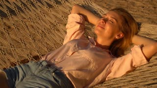 Slow motion model girl lying on hammock swinging, attractive young woman relaxing during break. Concept of tourism, modeling and travelling. Pretty lady without makeup smiling enjoying good weather