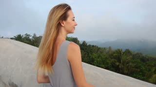 Slow motion programmer female relaxing among nature, young woman on long-awaited vacation abroad after working year. Concept of holidays, tourism or travelling. Smiling lady with fair hair enjoying