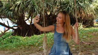 Slow motion teacher girl taking selfies with smartphone swinging in garden, female relaxing in shadow near sea beach. Concept of photography and gadgets or travelling. Attractive lady without makeup