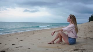 Slow motion translator girl sitting on sand near rolling sea waves, female come back home after long business trip. Concept of relax at seashore, travelling and tourism. Fair-haired lady enjoying