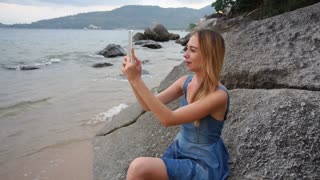 Slow motion traveler female with tablet shooting video, lady collecting content for social networks. Concept of innovative technologies, gadgets and holiday at sea. Young attractive woman with fair
