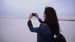 Slow motion traveler girl using smartphone making photos of sunset