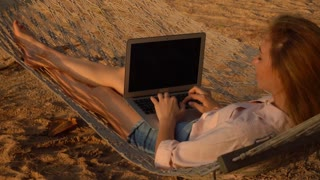 Slow motion writer young woman with laptop lying on hammock in shadow, fair-haired girl writing novel during vacation. Concept of innovative technologies, travelling and gadgets. Concentrated female