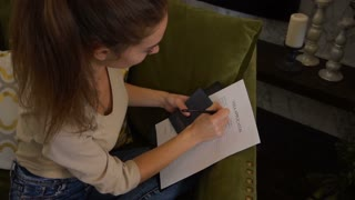 Slow motion young business woman with passport filling visa application form, female go to other country for work. Concentrated fair-haired girl with ponytail siting on green sofa at home. Concept of