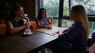 Smiling woman sits in front of two business women and telling about work s skills. Girls drink coffee and talking. Lady with long fair hair dressed in denim shirt. Concept of good working conditions
