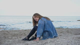 Smiling young woman alone relaxes sitting by sea and admires nature around on sandy beach with seashells in afternoon