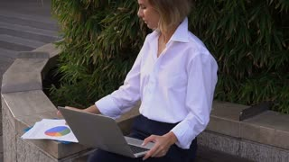 Statistician working outside with laptop and color diagrams