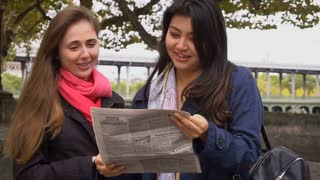 Students looking for job and reading newspaper outside