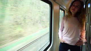 Stunning young woman looks and poses in camera, laughs and smiles showing gesture with thumb up and continues to look in large window moving at speed of modern train, enjoying trip. Woman of European