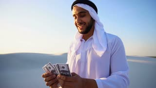 Successful Arab sheikh considers banknotes and happy, standing in center of sandy desert on warm summer day