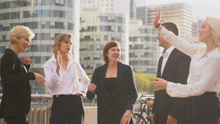 Successful business team greeting each other with good result outside in slow motion