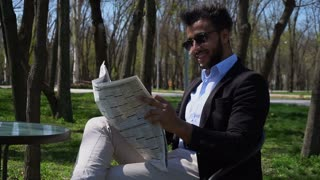 Successful businessman reading newspaper at lunch