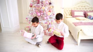 Sunny morning after Christmas and exchange of presents by siblings sitting on floor in bedroom with Christmas tree