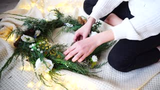 Talented girl completes design of New Year pine wreath, complements it with flowers and spruce branches, cones and artificial ornaments and prepares gift for friend on Christmas Eve. Young woman sits