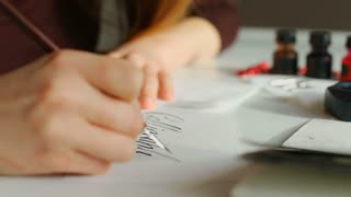 Teacher of art school prepares for lesson of correct and beautiful writing