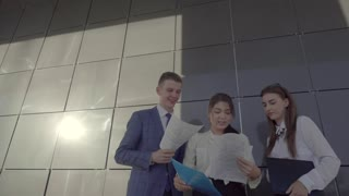 Three Business Professionals Female and Male, Speaks and Holding Paper, Stand on Background of Wall of Business Center Outside in Neutral Colors.