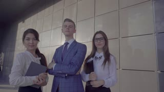 Three Educated Young Business People Posing at Camera With Folder in Hands on Background of Wall Near Business Center Outdoors in Neutral Colors.