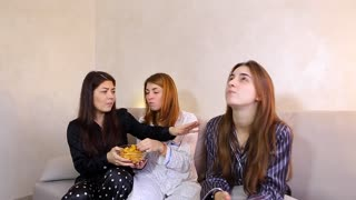 Three friends eating junk food potato chips. One girl hesitate because lady is on diet. Person is on vegan food nutrition