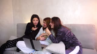 Three wonderful women look at computer comedy and eat popcorn, laugh and talk on girlish themes, pose in camera with smile on their face, sitting on gray soft sofa in bright bedroom at night. European